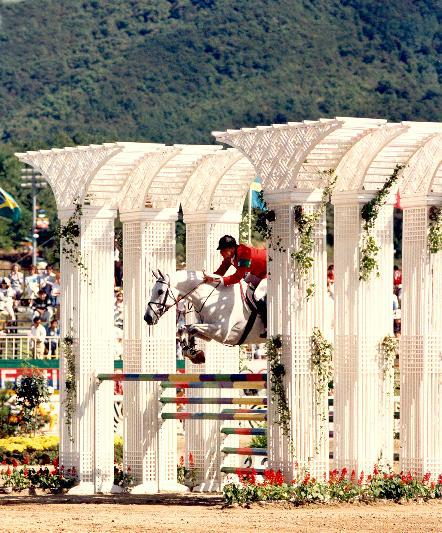 photo of Greg Best on Gem Twist jumping over a huge fence at the 1988 Olympics